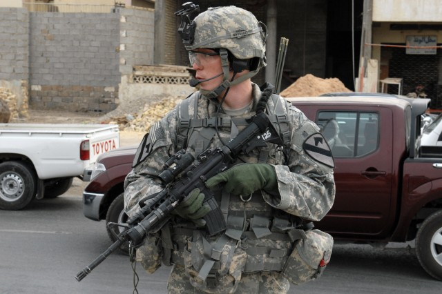 BAGHDAD - Pfc. Daniel Owen, from Eden Rapids, Mich., Company B, 2nd Battalion, 5th Cavalry Regiment, scans the area after dismounting a Mine-Resistant Ambush-Protected vehicle in Sadr City, April 26. The main objective of Co. B's patrol was to discourage any insurgent activity by providing a presence in the community.