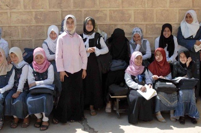 A group of girls are gathered in the shade of the Al Shaheed Hassan School in Muhallabiyah, Iraq. The school reopened after its renovation that was organized by local civic leaders, the local Iraqi Police and Iraqi Army and Coalition Force units in the area.
