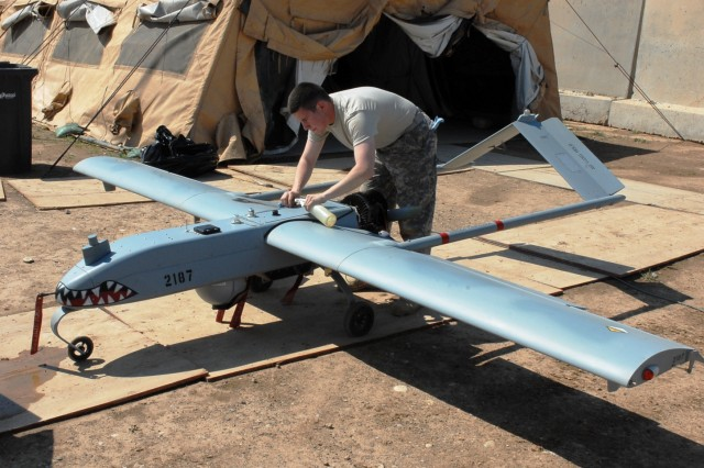 """Spc. Stephen Heinz, a Manassas, Va., native and unmanned aerial vehicle maintainer and operator for Company A, 2nd Special Troops Battalion, 2nd Brigade Combat Team, 1st Cavalry Division, cleans a UAV, April 12, on Forward Operating Base Warrior. The UAVs provide aerial reconnaissance capabilities and give Soldiers on the ground an extra """"eye in the sky."""""""