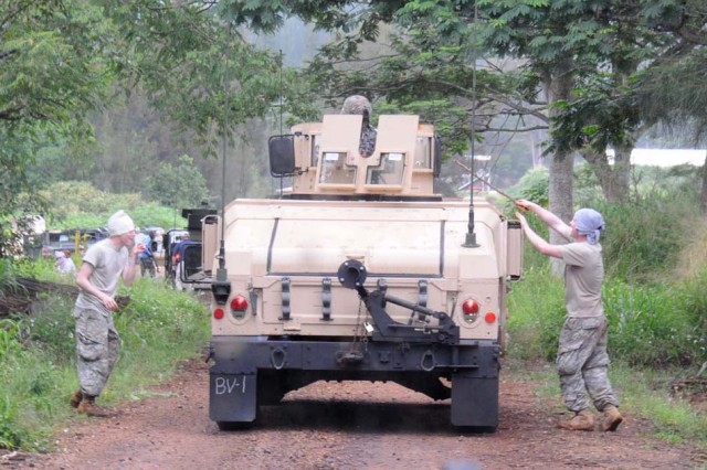 Soldiers from the 130th Engineer Brigade move down the road as locals rush up to their humvees during improvised explosive device lane training, April 23, at Schofield Barracks, Hawaii.