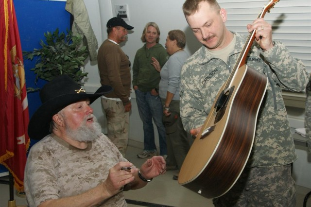 """Sgt. Don Carlson, truck commander, Headquarters and Headquarters Battery, 2nd Battalion, 146th Field Artillery, and Raymond, Wash., native, hands his guitar to Charlie Daniels for an autograph after a performance at the Morale, Welfare and Recreation base complex at Contingency Operating Base Q-West, Iraq, April 18. The Charlie Daniels band performed a two-hour show for more than 600 Soldiers, Airmen and civilians at Q-West. Soldiers rock-a-billied to classics like """"The Devil went down to Georgia,"""" and even a cover of Johnny Cash's """"Folsom Prison Blues."""" Daniels then stunned the room with his version of the Star Spangled Banner, something he hadn't played at any of the other stops in Iraq. The rendition garnered Daniels a standing ovation from the packed room."""