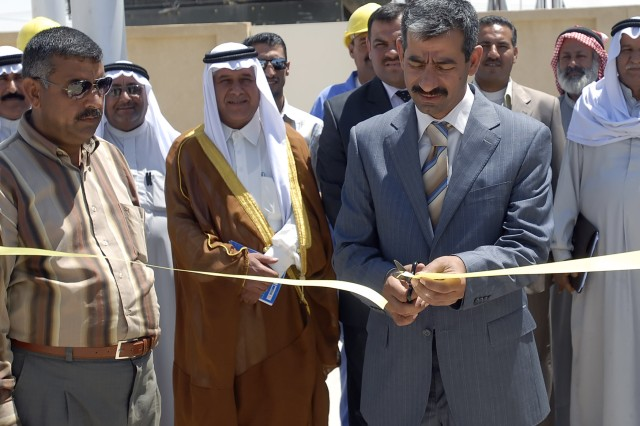 BAGHDAD - Kamil Abbas, the chairman of the Abu Ghraib District Council, cuts the ribbon at a ceremony signifying the opening of the Khandari Water Treatment Facility in Abu Ghraib April 27.