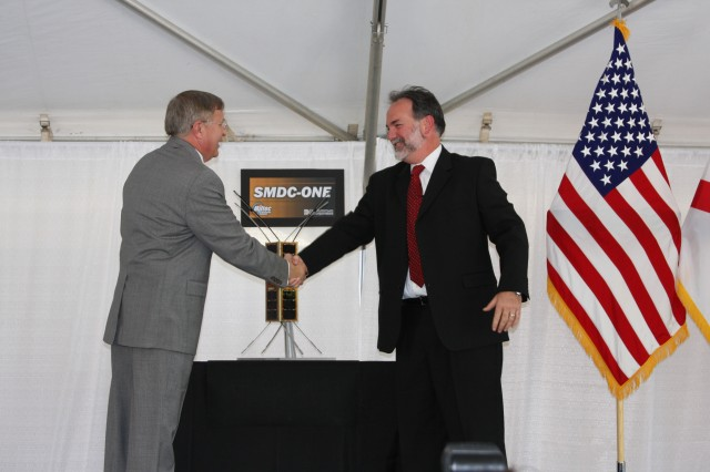 Dr. Steven Messervy, U.S. Space and Missile Defense Command/Army Forces Strategic Command deputy to the commander for Research, Development and Acquisition, left, and Ivy Pinion, senior vice president of Miltec Corporation, a Ducommun company, shake hands after the delivery to USASMDC/ARSTRAT of the Army Nanosatellite Technology Demonstration Program, which consisted of eight SMDC-ONE satellites. The first satellite will be placed in orbit in 2009, with the remainder placed at later dates.
