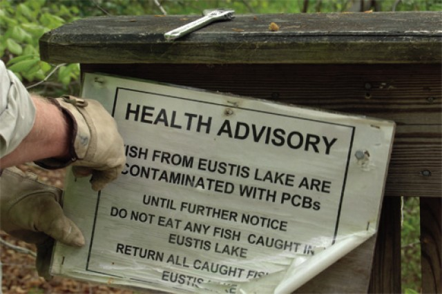 A volunteer removes a health advisory sign for replacement on a bridge on the Fort Eustis Nature Trail over Eustis Lake.
