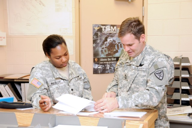 Master Sgt. Angelo Minardi, right, NCOIC at HHC 1st Bn., 223rd Avn. Regt. reviews tasking operations at Knox airfield with Sgt. 1st Class John Langley.