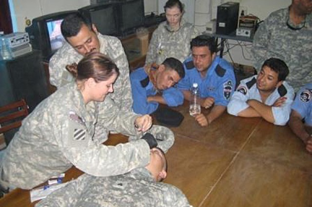 Spc. Krystal Elliott, 59th Military Police Company, demonstrates first aid procedures to Iraqi policemen. The 59th MP Company was recognized for their efforts in training and recruiting Iraqi policemen during the deployment there in 2007 and 2008.