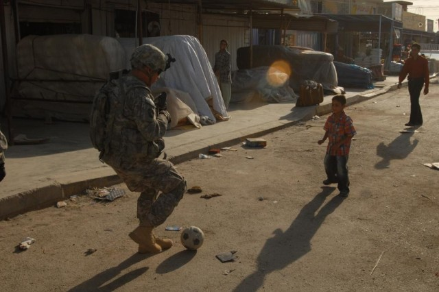 TAJI, Iraq - Staff Sgt. Steven Jones, of Bradford Pa., takes time to kick back a soccer ball while on patrol in Taji Market with Company C, 1st Battalion, 112th Infantry, 56th Stryker Brigade Combat Team, 1st Cavalry Division, Multi-National Division - Baghdad.