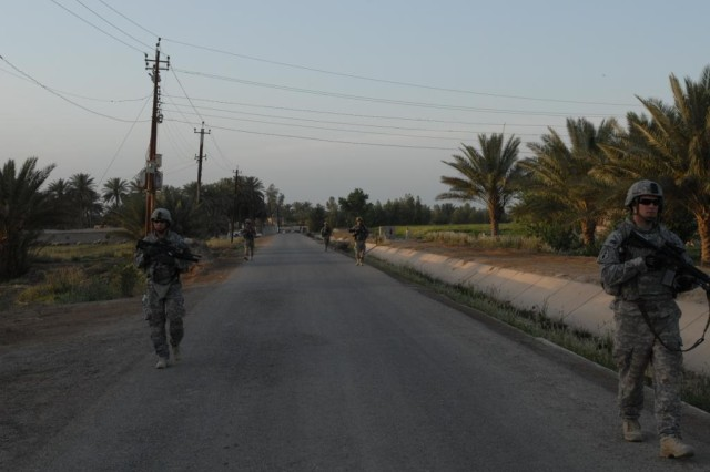 TAJI, Iraq - Members of Company C, 1st Battalion, 112th Infantry, 56th Stryker Brigade Combat Team, patrol a main road in the town of Zorba, Iraq, before returning to their Joint Security Station in Hor al-Bosh.