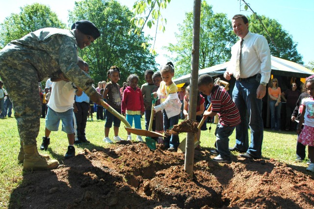 Col. Deborah Grays, U.S. Army garrison commander, plants a flowering cherry tree at Jacobs Park on Fort McPherson April 24 with a little help from children in the pre-k class at the Child Development Center as Owen Nuttall (right), chief of the Base Realignment and Closure Environmental Office, watches.  The children later planted some zinnia plants, also as part of the Earth Day celebration.