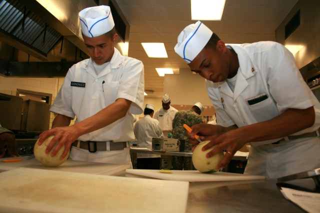 FORT CARSON, Colo.-Pvt. Carlos Gonzalez, 1st Brigade Combat Team, 4th Infantry Division, left, and Spc. Charles Wells, 183rd Maintenance Company, practice carving techniques on honeydew melons.