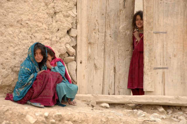 Afghan children wait for a truck with humanitarian aid supplies to be unloaded in Panow, Paktika Province, Afghanistan, June 27, 2007.