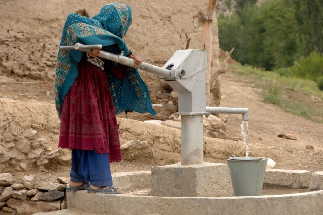 An Afghan girl pumps water in Panow, Paktika Province, June 27, 2007. Afghan soldiers built the water pump to help their fellow Afghans.