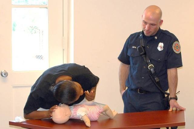 Biehl watches Christina Leak check for a pulse and feel for the baby's breath as part of infant CPR.  Leak is married to Master Sgt. (Ret.) Kelvin Leak.