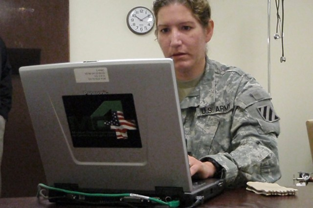 Capt. Christina Johnson, physician assistant at the 3rd IDAca,!a,,cs Special Troops Battalion Aid Station, Fort Stewart, Ga., uses the MC4 system to document SoldiersAca,!a,,c medical information and review their medical history.
