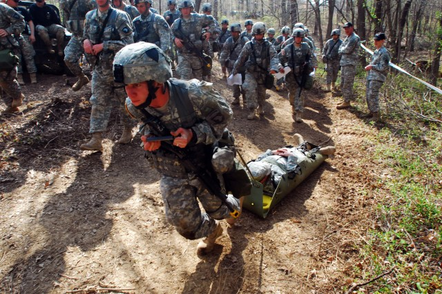 With his peers closely watching, Spc. Joshua Matienzo, with Company C, 526th Brigade Support Battalion, 2nd Brigade Combat Team, 101st Airborne Division (Air Assault), maneuvers a casualty up a hill using the SKED litter during week-one of the Expert Field Medial Badge competition, April 16.
