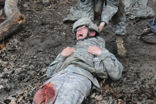 1st Lt. Tom Collins, 1st Battalion, 327th Infantry Regiment brings a wounded Soldier to cover during testing for the EFMB on April 22.
