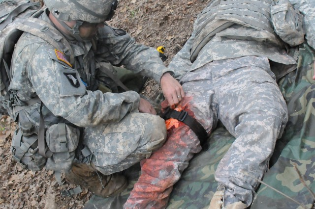 A 101st Airborne Division Soldier applies a tourniquet to stop the bleeding of a leg wound during EFMB testing, April 22.