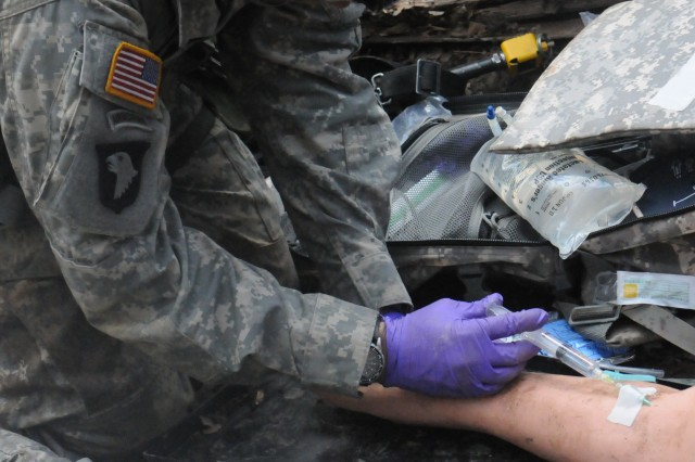 A 101st Airborne Division Soldier injects fluid into the arm of a simulated injured Soldier's arm during EMMB testing on April 22.