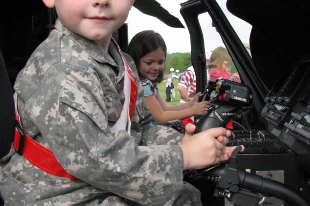 "Wearing a uniform similar to his dadAca,!a,,cs Army ACUs, 4-year-old John Gavigan strikes a Soldier pose at the controls of a Black Hawk Medevac helicopter during Bring Your Child to Work Day. He is the son of Capt. John Aca,!A""JayAca,!A? Gavigan."