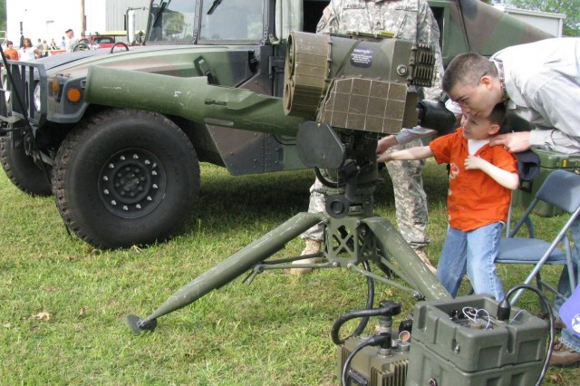 Josh Call of AMC Headquarters helps his son, 5-year-old Jensen, look though the Humvee Mounted Improved Target Acquisition System during Bring Your Child to Work Day. In the background is Staff Sgt. John Rankin.