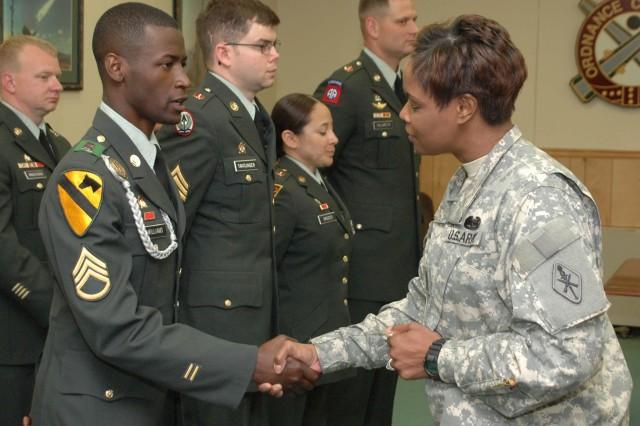 Command Sgt. Maj. Angel Clark-Davis, 59th Ordnance Brigade command sergeant major, congratulates the NCO of the Quarter, Staff Sgt. Scottie Williams of 73rd Ordnance Battalion.