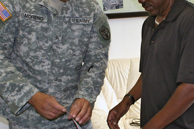 Sgt. Jonathan Moreno works with mentor and Information Technology specialist Gregory Reedy on how to install computer hardware. Moreno, a Soldier with the U.S. Army Garrison Bamberg, Germany, Warrior Transition Unit, is using his recuperation time to learn new skills for his return to the civilian workforce.