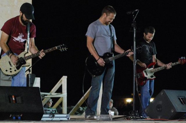 The Orange County Calif., rock band, Hollowell, jammed for Soldiers at the Favors Outdoor Theater at Contingency Operating Base Q-West, Iraq, April 10, in the first outdoor show of the year at this remote Army logistics base in northern Iraq. Band members included Joe Denges, lead vocals and guitar; Matt Hulet, lead guitar; Justin Dike, drums; and Dusty Schiefelbein, backup vocals and bass guitar.