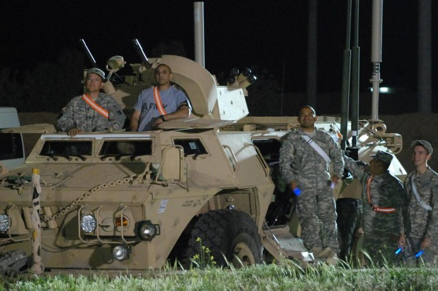 California Guardsmen from Echo Company, 1st Battalion, 185th Armor, use their armored security vehicle as seating during the Hollowell concert at the Favors Outdoor Theater at Contingency Operating Base Q-West, Iraq, April 10. Hollowell, a progressive rock band out of Orange County, Calif., band members included Joe Denges, lead vocals and guitar; Matt Hulet, lead guitar; Justin Dike, drums; and Dusty Schiefelbein, backup vocals and bass guitar.