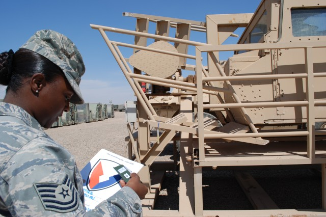 Air Force Tech. Sgt. Tamekah Burrell, container management noncommissioned officer at the 2nd Battalion, 402nd Army Field Support Brigade at Joint Base Balad, Iraq, holds an Army Materiel Command decal and a radio frequency identification tag that will be attached to a vehicle destined for transportation from the Retrograde Property Assistance Team yard at Balad to the holding yards at Camp Arifjan, Kuwait. The decals and RFIDs make it easier to track AMC assets.