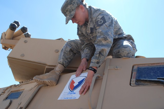 Air Force Tech. Sgt. Christy Long, quality assurance noncommissioned officer at the 2nd Battalion, 402nd Army Field Support Brigade at Joint Base Balad, Iraq, places an Army Materiel Command decal on a vehicle that will be shipped to the Retrograde Property Assistance Team holding yard at Camp Arifjan, Kuwait, pending shipment to its final destination.