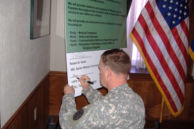 Col. Larry Heisler signs the Army Warrior Healthcare Covenant at Rock Island Arsenal, Ill.