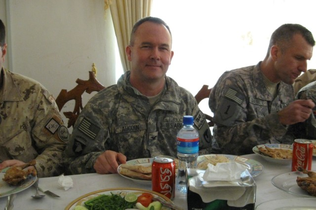 The author, Col. David Aucoin, shares lunch with fellow officers, hosted by an Afghan provincial governor. Note the markings on the otherwise familiar soda can.