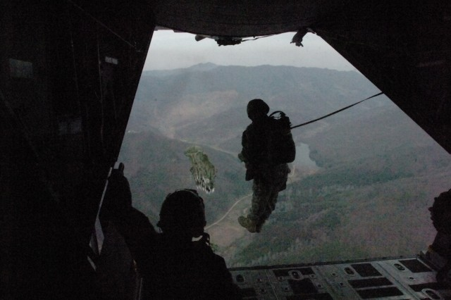 """A paratrooper with the 1st Special Forces Group (Airborne) exits a C-130 aircraft near Chongsong, South Korea, April 3, 2009, during a """"friendship jump"""" with the Republic of Korea 11th Special Forces Brigade. A """"friendship jump"""" occurs when members different countries military forces execute a parachuting operation together in peacetime."""