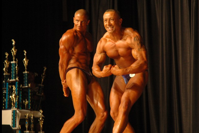 Staff Sgt. Jeff Herzog (left) and Master Sgt. Bob Day show off their muscle power during the 26th Annual Armed Forces Hawaii Bodybuilding Championship at Pearl Harbor, Hawaii, Saturday. Herzog placed first and Day placed second in the men's middleweight division.
