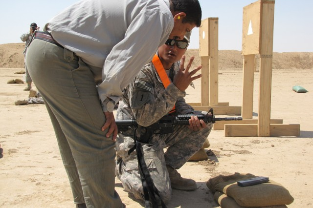 Sgt. Jerry Agonoy of Company A, Special Troops Battalion, 3rd Infantry Brigade Combat Team, 25th Infantry Division, explains the fundamentals of basic rifle marksmanship to a Sons of Iraq member at Forward Operating Base Bernstein, April 19. Soldiers from Co. A coached and competed in a shooting tournament with SoI and members of the Iraqi Army and Iraqi Police to help strengthen relationships.