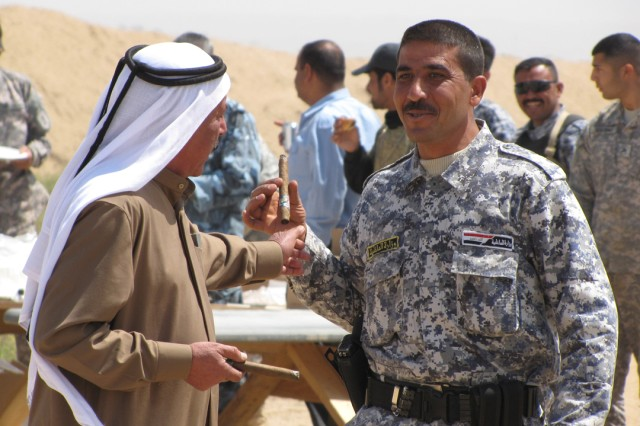 Shaykh Husayn Awad Khalaf hands a celebratory cigar to an Iraqi policeman at a marksmanship competition with Coalition and Iraqi Security Forces at FOB Bernstein April 19.  The event was sponsored by Co. A, Special Troops Bn., 3rd Inf. Bde. Combat Team, 25th Inf. Div., to strengthen relationships that will last long after Coalition Forces depart Iraq in 2011.