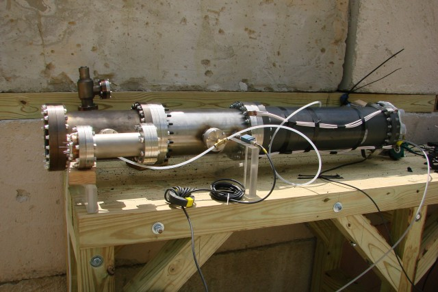 This is the completely assembled autonomous explosive driven high power microwave system. The flux compression generator is on the other side of the wall. Left to right: high power microwave tube, high voltage measurement chamber, and power conditioning unit (inductive store, exploding wire opening switch, and spark gap closing switch).