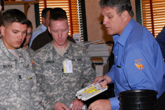 Capt. Richard Becker, 275th Signal Company, and Capt. Jason Carlile, 362nd Signal Company, take an opportunity to network with one of several industry partners present at the LandWarNet Conference April 14-16, at Camp Stanley.