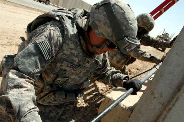 Engineers with the 180th Engineer Co., Virginia Army National Guard, move a concrete T-wall into place along Main Supply Route Tampa, near Convoy Support Center Scania, Iraq April 17. Coalition forces will return MSR Tampa's southbound lanes to the Iraqi government this summer