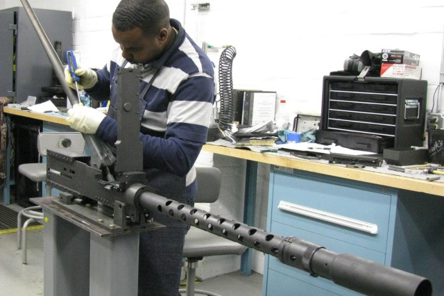 David Forrest of AMCOM's Maintenance Operations Procedures and Prototype facility (MOPP Shop) reassembles a M3P 50 caliber machine gun that was once used on an Avenger air defense system. As the Army restructures and takes out of service the Avengers, these machine guns are being reconditioned and reassembled, quality checked, and test fired at Test Area 1 and then mounted on a Kiowa Warrior helicopter.