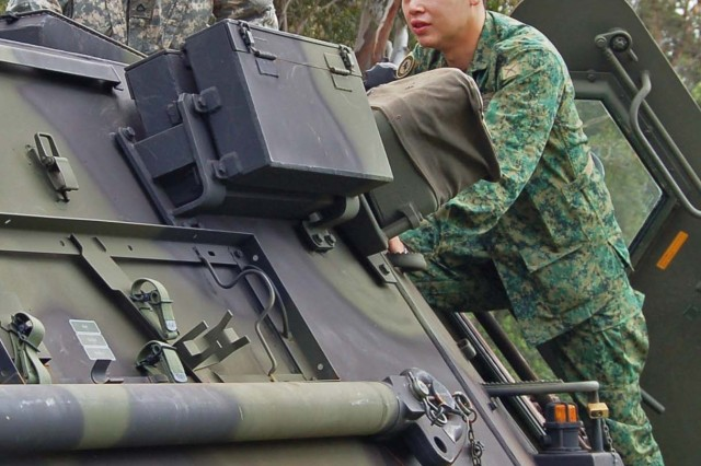 Pfc. Justin Bolek, a chemical operations specialist with the 71st Chemical Company, answers question from a Soldier in the Singapore Army during a M903A1 Fox vehicle demonstration.  During the visit, Singapore Soldiers learned about the vehicle and were able to ride in them as well.