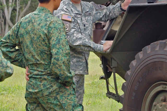 Col. Heok Chye Lee, commander of the Chemical Biological Radiological Nuclear and Explosive Defense Group in the Singapore Army (left), and Lt. Col. John Riley, the Chemical Biological Radiological Nuclear and Explosive Division chief at U.S. Army Pacific Command, talk about the M903A1 Fox vehicle during a visit Tuesday, April 28.  The visit highlighted an exchange of information between the two armies.