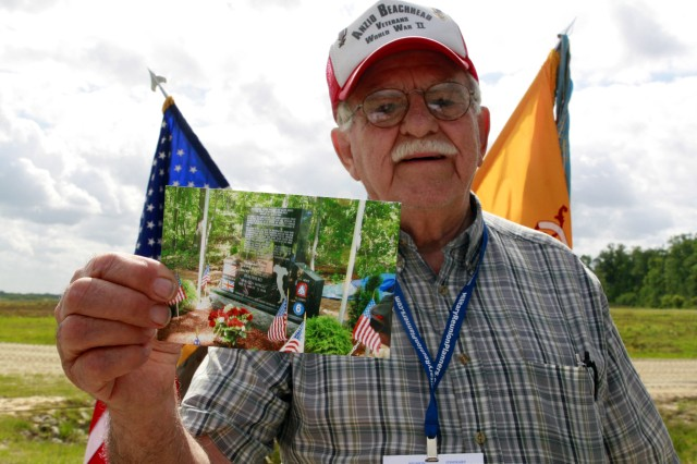 At Fort Stewart's firing range Red Cloud Alpha, Jim Luzzi describes his experiences during World War II as he holds up a photo of the Anzio Beachhead Veterans memorial that he helped build, April 28