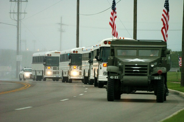 """The buses are led in by 4th Infantry Division's half track as hundreds of families, friend and fellow Soldiers wait for them to arrive home from Iraq May 4, in front of the 4th Inf. Div. Headquarters. A small contingent of Soldiers from the 4th Brigade Combat Team, 1st Cavalry Division's """"torch party"""" also arrived to a heroes' welcome."""