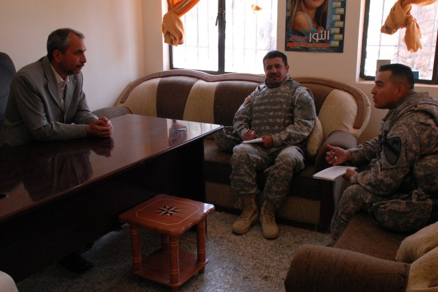 Sgt. 1st Class Miguel Casarez (right), San Antonio, Texas native, and a platoon sergeant in 4th Squadron, 9th Cavalry Regiment, 2nd Brigade Combat Team, 1st Cavalry Division, meets with Salah Wahiz Hassad, a teacher at a primary school in Arab Kuy village, Daquq, Iraq, April 21. Casarez met with school officials to assess the security of the school and determine what supplies the school might need.
