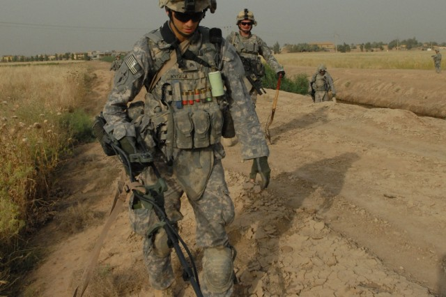 TAJI, Iraq - Pittsburgh native, Sgt. Daniel Kysela of Company C, 1st Battalion, 112th Infantry Regiment, 56th Stryker Brigade Combat Team, uses a metal detector to search for weapons caches May 4 near Taji, north of Baghdad. Kysela is followed by Spc. John Schloder of Ridgeway, Pa., who has a shovel at the ready to investigate alarms from the detector.