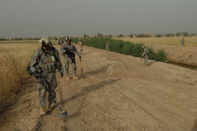 TAJI, Iraq -Sgt. Daniel Kysela of Pittsburgh operates a metal detector May 4 along a canal near Taji, just north of Baghdad. The Soldiers, with Company C, 1st Battalion, 112th Infantry Regiment, 56th Stryker Brigade Combat Team, were searching for weapons caches.