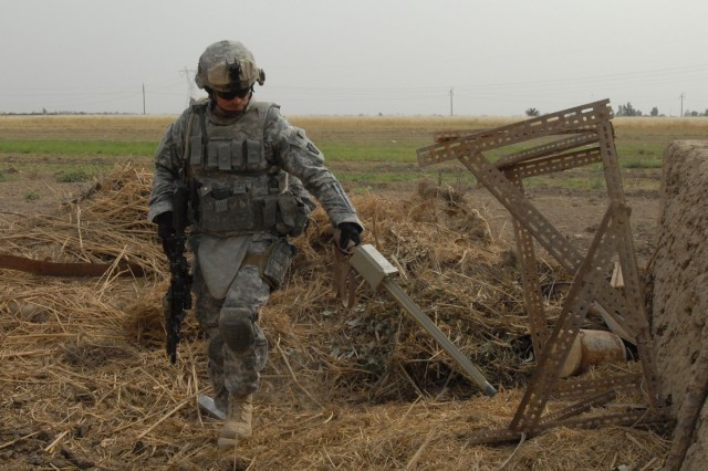 TAJI, Iraq - Spc. John Schloder of Ridgeway, Pa., from Company C, 1st Battalion, 112th Infantry Regiment, 56th Stryker Brigade Combat Team, runs a metal detector searching for weapons caches May 4 at a farm near Taji, just north of Baghdad.