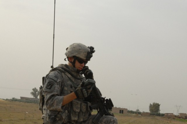 TAJI, Iraq - Spc. Adam Feldon of Allentown, Pa., from Company C, 1st Battalion, 112th Infantry Regiment, 56th Stryker Brigade Combat Team, mans a radio in a rural area near Taji, north of Baghdad, during a search for weapons caches May 4.