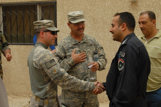 BAGHDAD - Trenton, N.J. native, Maj. Robert Arnold (left), a military policeman assigned to Headquarters and Headquarters Company, 8th Military Police Brigade, Multi-National Division-Baghdad, greets Cpt. Hassam al-den Falah, the maintenance officer for the water patrol in the district of al-Karkh May 6.  Hassam is responsible for repairing the boats from the al-Karkh water patrol.